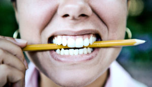 woman biting pencil (negotiations concept)