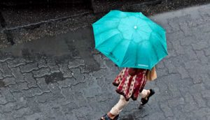 woman with umbrella walking in Mumbai (urban development and rainfall concept)