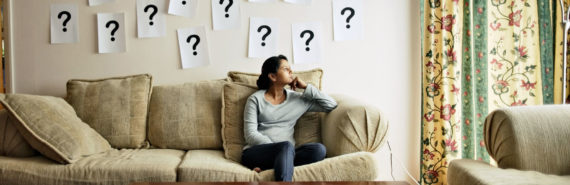 woman on couch with question marks on wall
