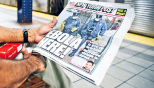 hands hold New York Post with Ebola headline