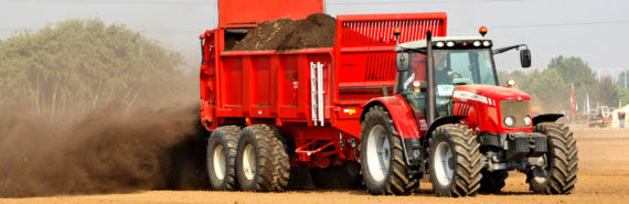 red tractor sprays manure on field - antibiotics in manure