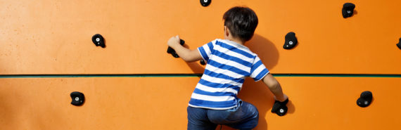 boy on orange climbing wall