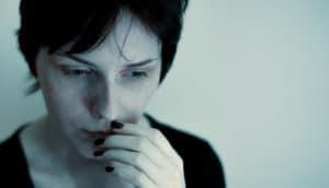 depression - sad woman in dim light