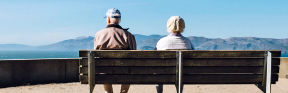 elderly couple on bench facing away - dementia concept