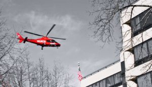 red helicopter approaches building