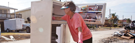 woman cleans fridge after hurricane - housing recovery