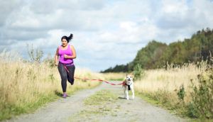 woman runs with dog - exercise and happiness