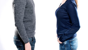 man and woman standing face to face (belly fat concept)