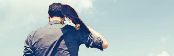 man faces away holding skateboard