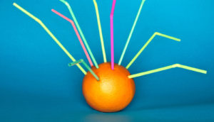 straws stuck in an orange
