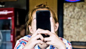 phone covering woman's face (online privacy concept)