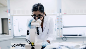 scientist with microscope in the lab