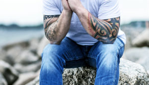 seated man with tattoos