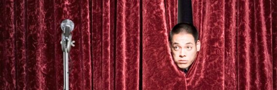 man behind curtain on stage
