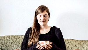 woman sitting on couch eyes closed (irritable bowel syndrome concept)