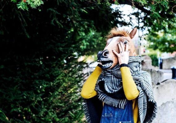 woman wearing horse mask (horses and influenza concept)