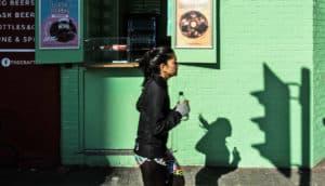 woman jogs by green wall