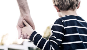 young boy holding hands (autism concept)
