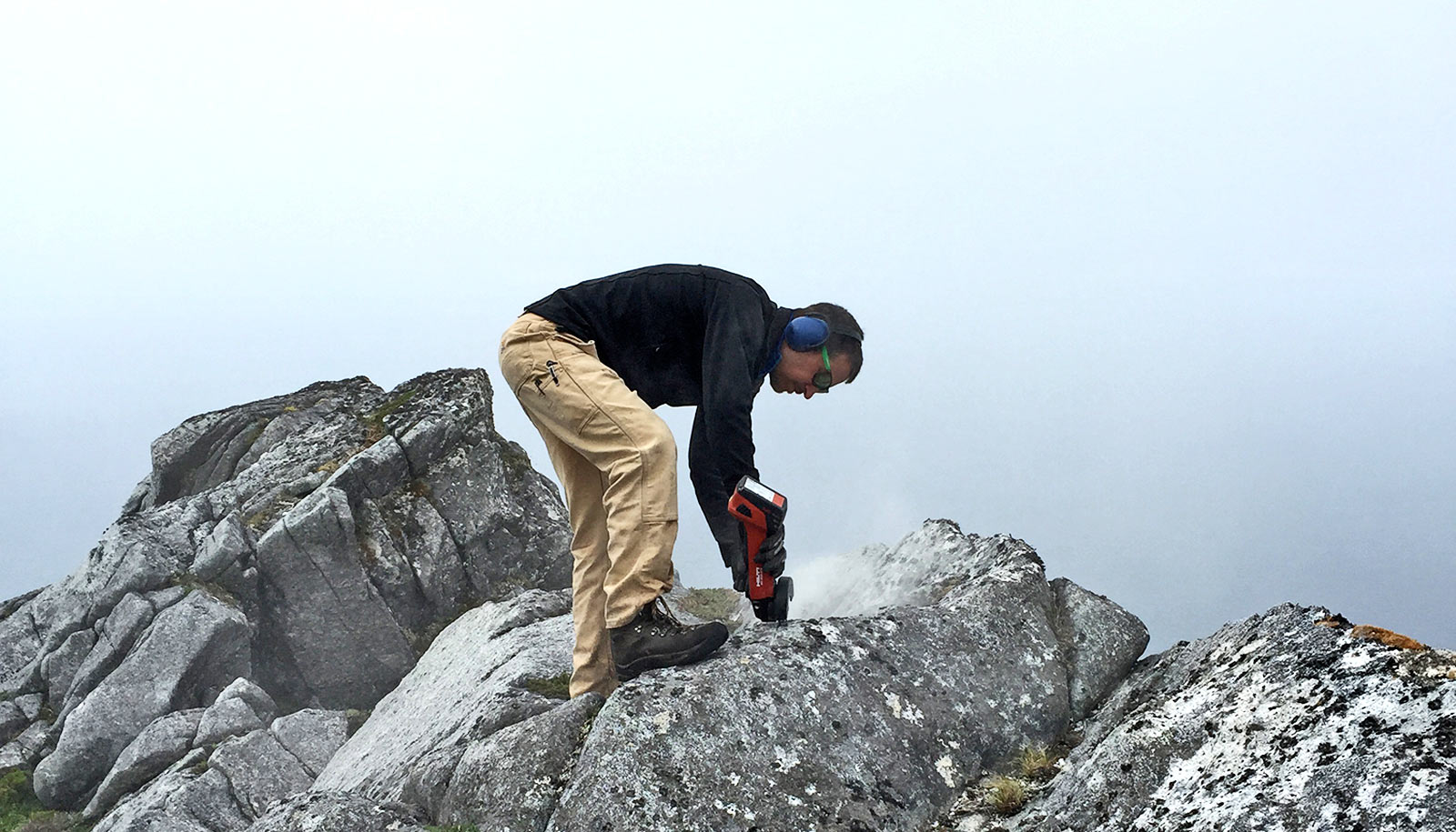geologist bends to drill into rock
