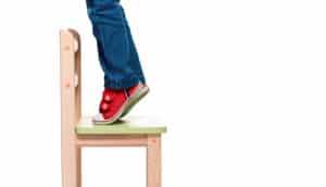 child standing on chair - gun safety