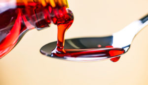 red cough medicine pouring into spoon