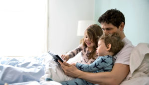 dad with two toddlers in bed - apps for preschoolers