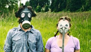 man and woman in gas masks - behavioral immune system