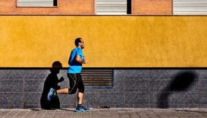 man running past orange wall