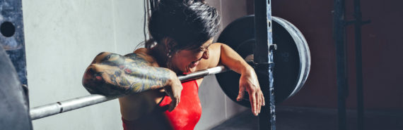 woman makes face while lifting weights - lactate
