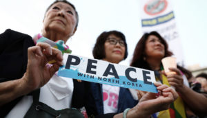 """activists hold """"peace with north korea"""" sign"""