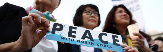 "activists hold ""peace with north korea"" sign"