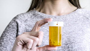 woman holding up pill bottle (breast cancer concept)