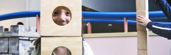 girl looks through wooden block tower - block play