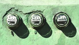 electricity meters on green wall
