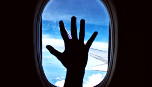 hand on airplane window (airplane cabins concept)