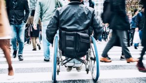 Man in wheelchair on busy street (multiple sclerosis concept)