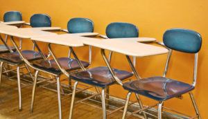 blue school desks against orange wall