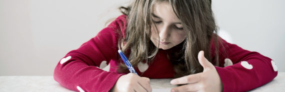 girl in pink sweater doing math