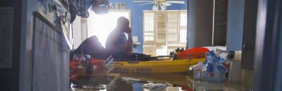 man in kayak in house during Hurricane Harvey