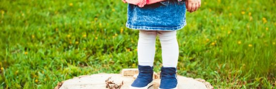 toddler stands on tree stump