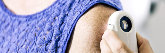 dermatologist examines woman's arm