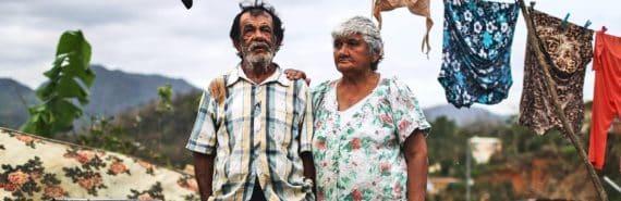 couple looking over hurricane maria damage