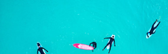 four surfers in black from above
