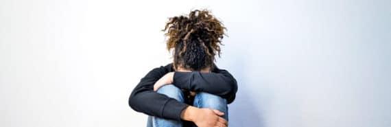 teen girl hugs her knees - abortion fund