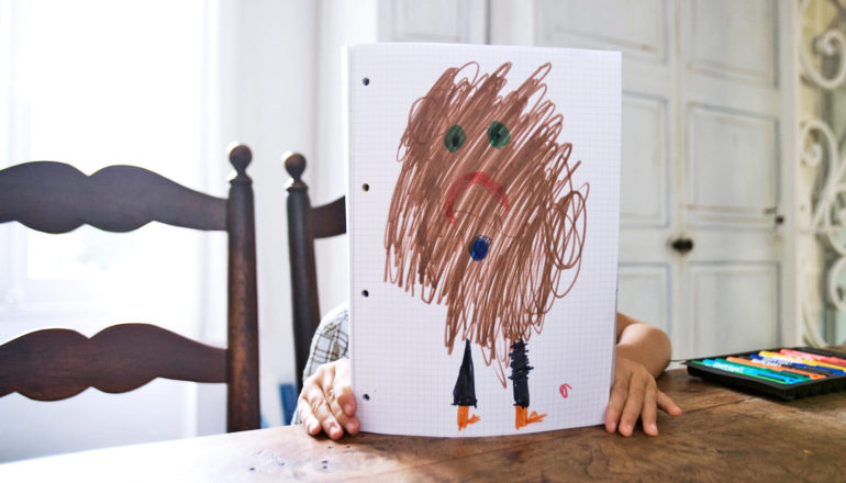 child behind drawing of brown sad blurry person