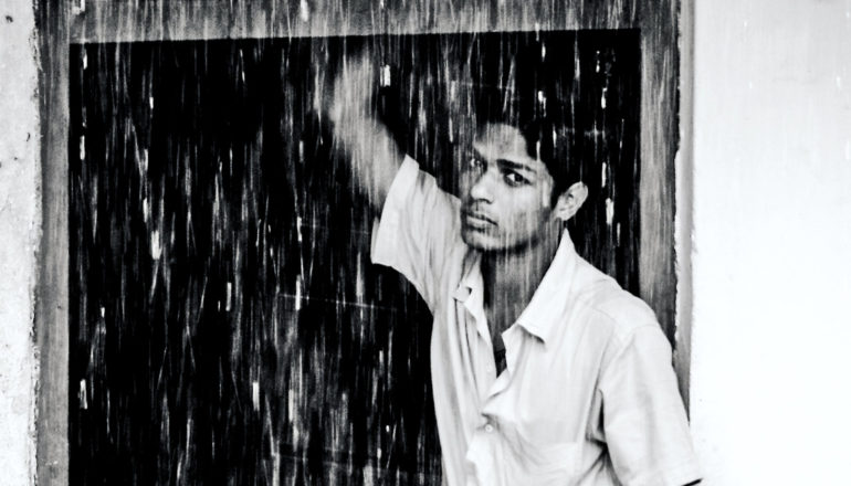 man looking out at monsoon