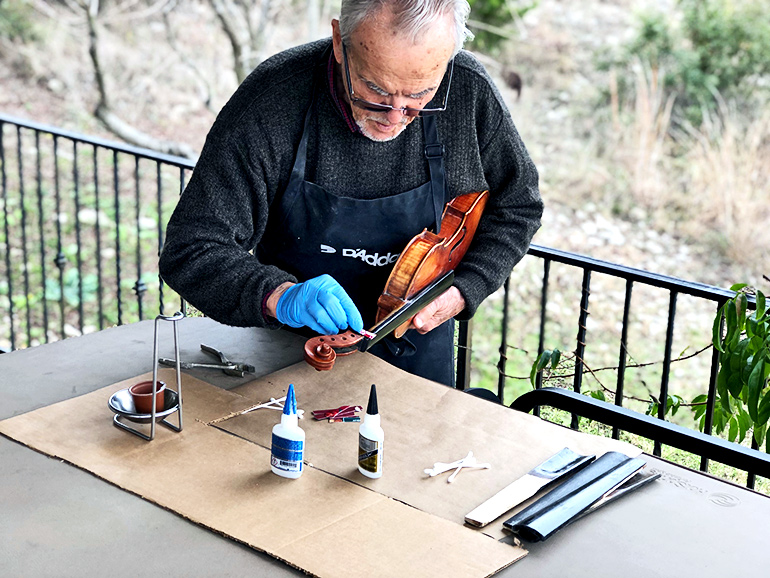 Nagyvary applies glue to a violin fingerboard