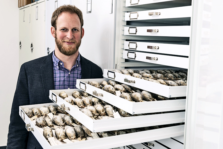 Benjamin Winger with some of the migratory songbirds researchers used in the study