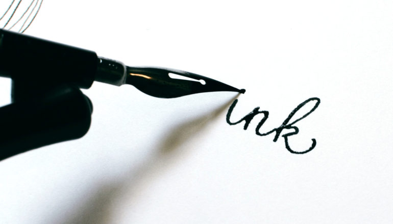 """pen writes the word """"ink"""" on white paper"""