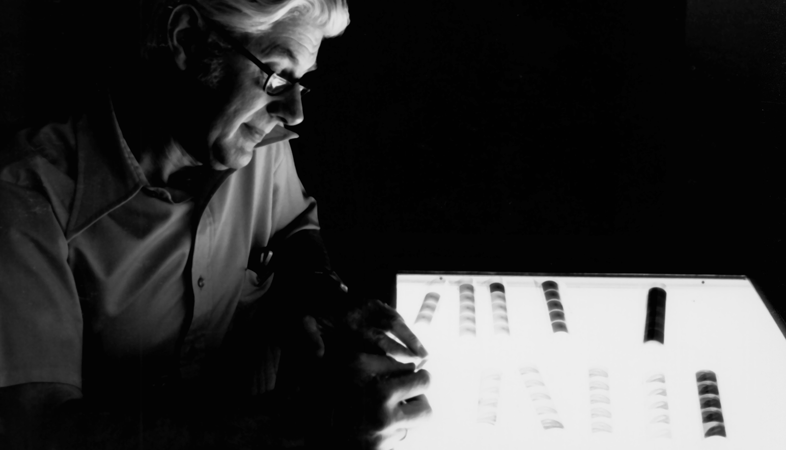 man looks at negatives on lightbox